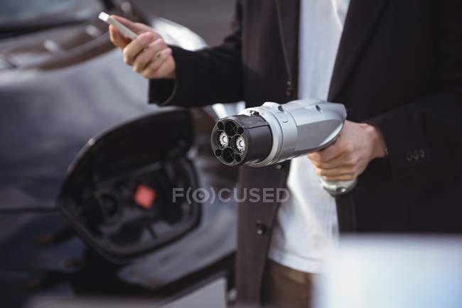 Mittleren Bereich der Mann mit Handy Autoladegerät an Ladestation Elektrofahrzeug mit gedrückter — Stockfoto