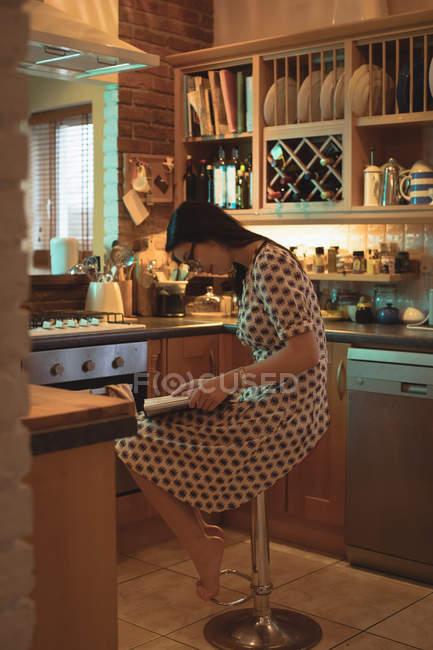 Frau liest ein Buch in der Küche zu Hause — Stockfoto