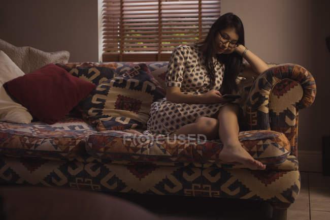 Frau benutzt Handy auf Sofa im heimischen Wohnzimmer — Stockfoto