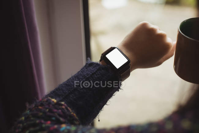 Woman looking at smart watch while having coffee at home — Stock Photo