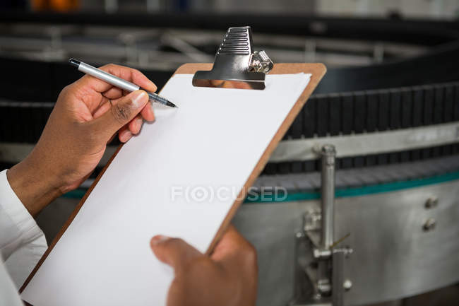 Mid section of man noting on clipboard at juice factory — Stock Photo