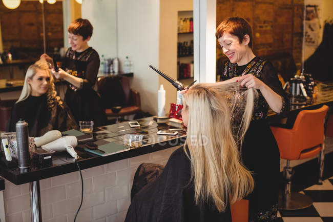 Female hairdresser styling clients hair in saloon — Stock Photo