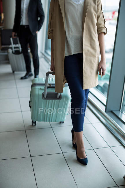 Businesswoman with luggage walking through waiting area at airport — Stock Photo