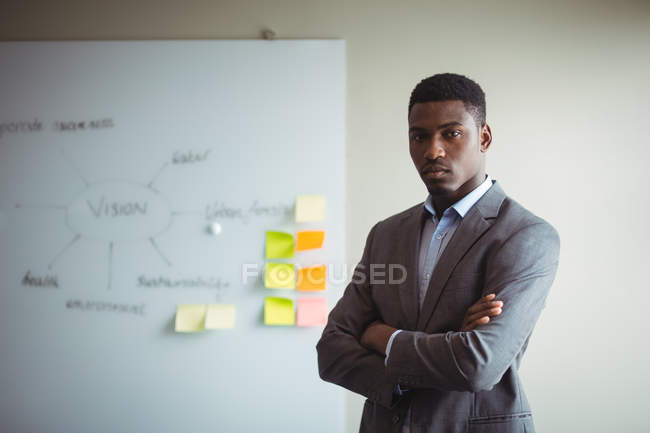 Portrait of businessman standing with arms crossed in office — Stock Photo