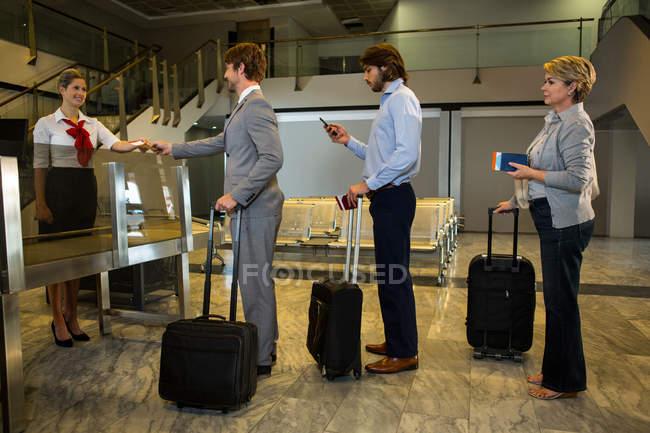 Personal control de embarque de pasajeros en el mostrador de facturación en el aeropuerto - foto de stock