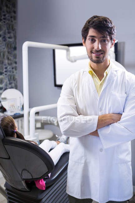 Portrait d'un dentiste souriant debout les bras croisés à la clinique dentaire — Photo de stock
