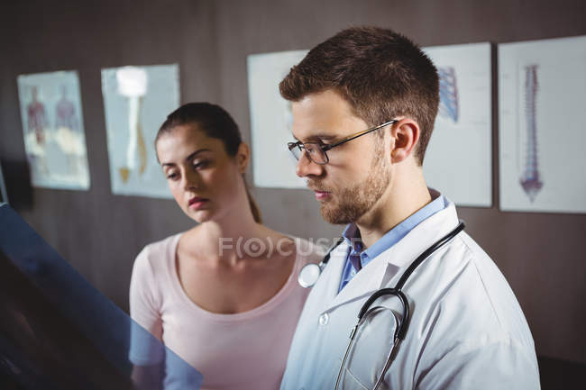 Fisioterapeuta e paciente do sexo feminino olhando para raio-X da coluna na clínica — Fotografia de Stock