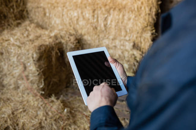 Cropped image of farm worker using digital tablet in barn — Stock Photo