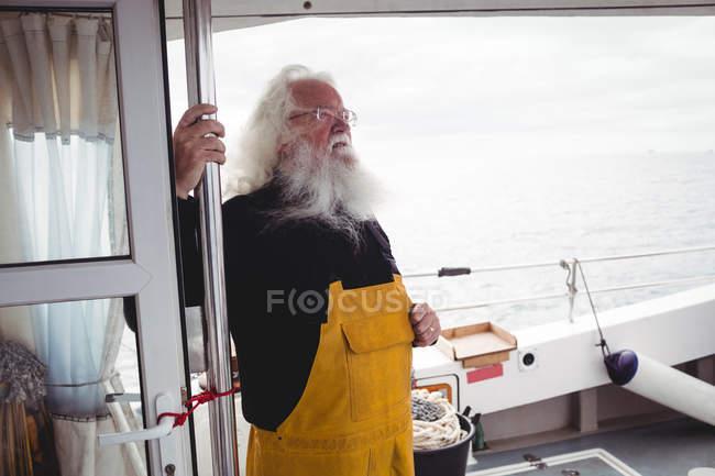 Nachdenklicher Fischer steht auf Fischerboot — Stockfoto