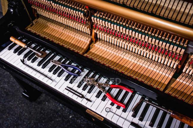 Nahaufnahme von Reparaturwerkzeugen auf alter Klaviertastatur — Stockfoto