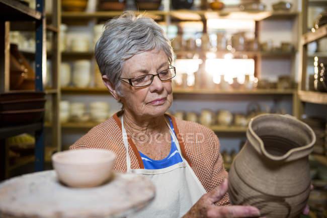 Горшечник проверяет горшок в мастерской по керамике — стоковое фото