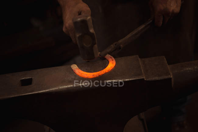 Hands of blacksmith working on a metal piece with hammer in workshop — Stock Photo