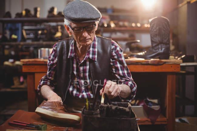 Shoemaker applying glue on shoe in workshop — Stock Photo