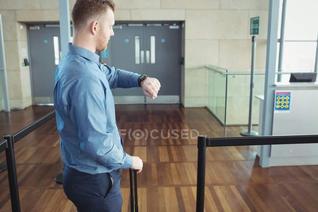 Чоловік стояв з багажем і час Реєструємося терміналу аеропорту — стокове фото