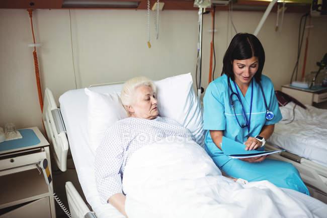 Krankenschwester interagiert mit Seniorin, während sie sich Bericht im Krankenhaus ansieht — Stockfoto