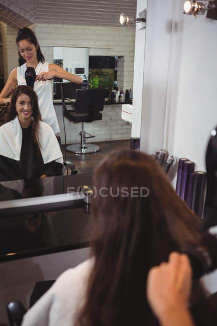 Donna che si fa asciugare i capelli con l'asciugacapelli dal parrucchiere — Foto stock