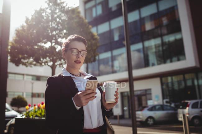 Jeune femme d'affaires utilisant le téléphone mobile par la route — Photo de stock