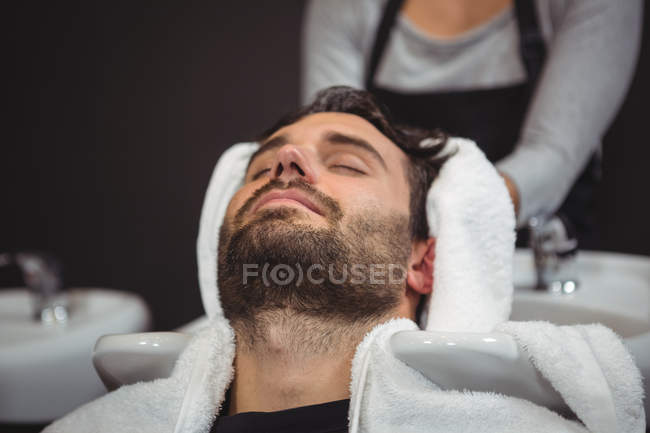 Estilista de cabello de hombre con la toalla en el salón de - foto de stock