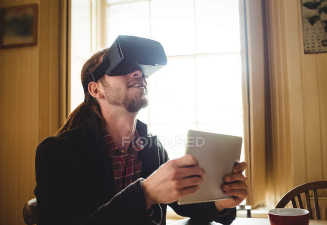 Hipster holding digital tablet while using virtual reality simulator at home — Stock Photo