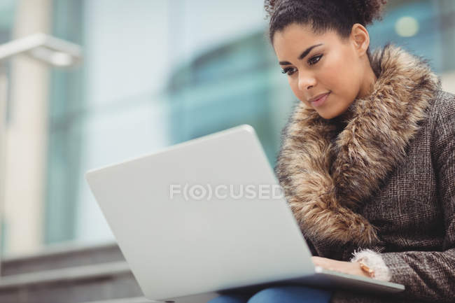 Low angle view of woman with laptop against building — Stock Photo
