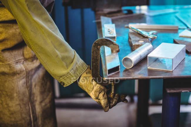 Обрезанное изображение женского сварщика с помощью зажима инструмента в мастерской — стоковое фото