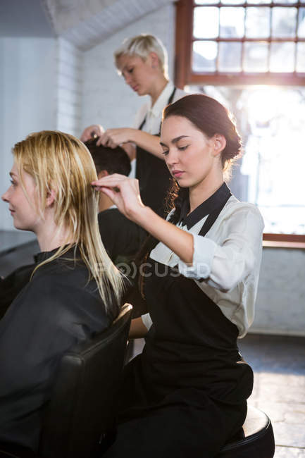 Coiffeur peigner les cheveux du client dans le salon — Photo de stock