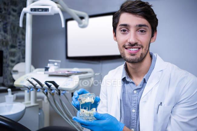 Dentista sorridente che tiene il modello della bocca alla clinica dentale — Foto stock