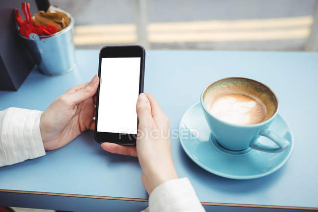 Cropped image of woman holding smartphone with blank screen in cafeteria — Stock Photo
