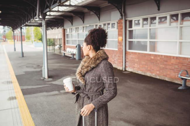 Женщина с одноразовой чашкой кофе стоит на платформе железнодорожного вокзала — стоковое фото