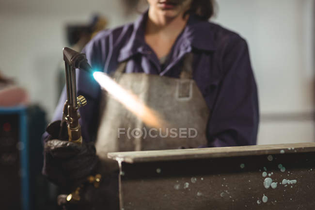 Midsection of female welder working with metal in workshop — Stock Photo