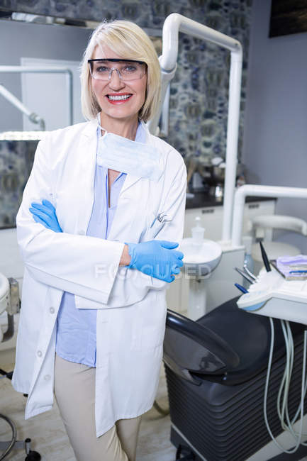 Portrait of smiling dentist standing with arms crossed at dental clinic — Stock Photo