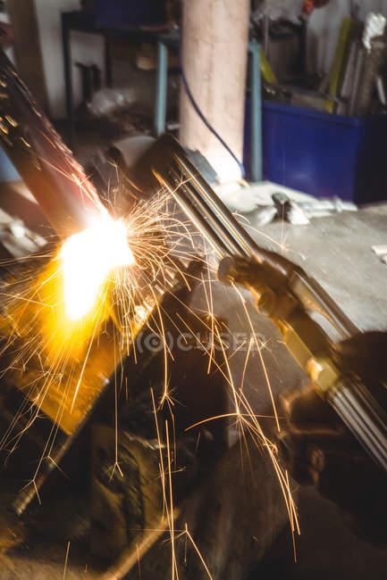 Искры во время сварки металла в цехе — стоковое фото