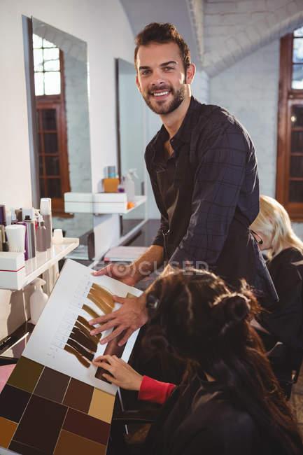 Femme sélectionnant la couleur des cheveux avec styliste au salon de coiffure — Photo de stock