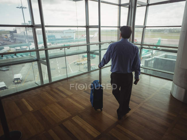 Rear view of businessman with luggage looking through glass window at airport — Stock Photo