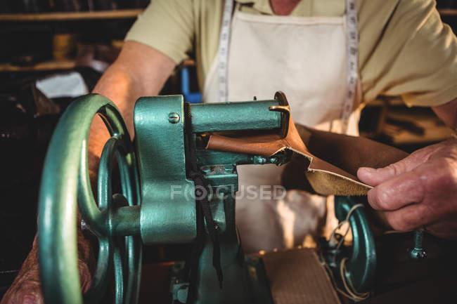 Seção média de sapateiro usando máquina de costura na oficina — Fotografia de Stock