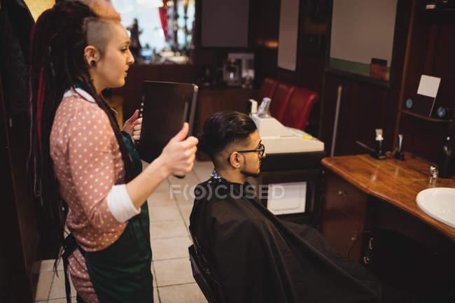 Femmina barbiere mostrando uomo il suo taglio di capelli nello specchio al negozio di barbiere — Foto stock