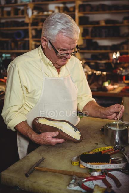 Shoemaker applying glue on shoe sole in workshop — Stock Photo