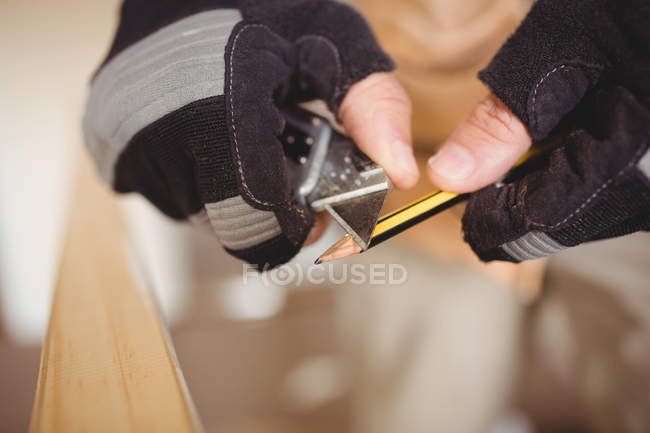 Cropped image of carpenter sharpening pencil — Stock Photo