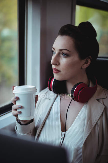 Thoughtful woman holding disposable coffee cup by window in train — Stock Photo