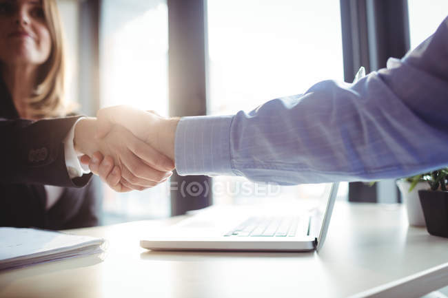 Кадроване зображення бізнес-леді потискують один одному руки з колегою в офісі — стокове фото