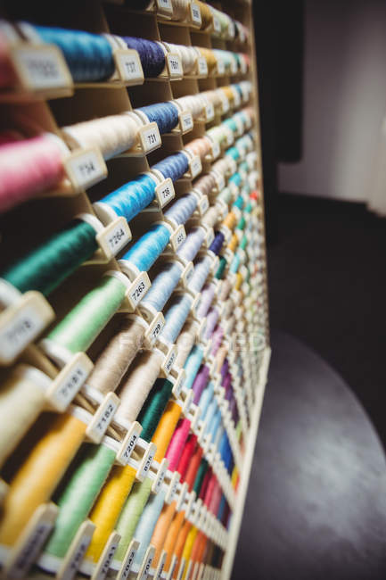 Colorful spools of threads in box in sewing studio — Stock Photo