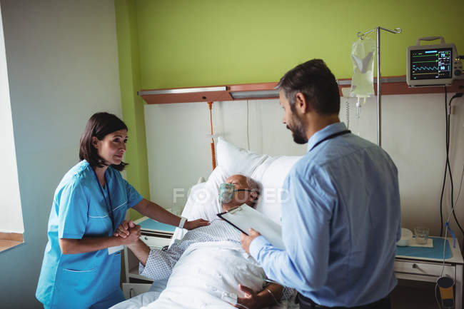 Медсестра утешает пожилого пациента с доктором в больнице — стоковое фото