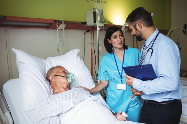 Enfermeira consolando paciente idoso com médico no hospital — Fotografia de Stock