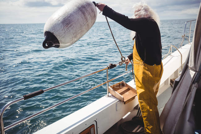 Fisherman throwing buoy into sea from fishing boat — Stock Photo