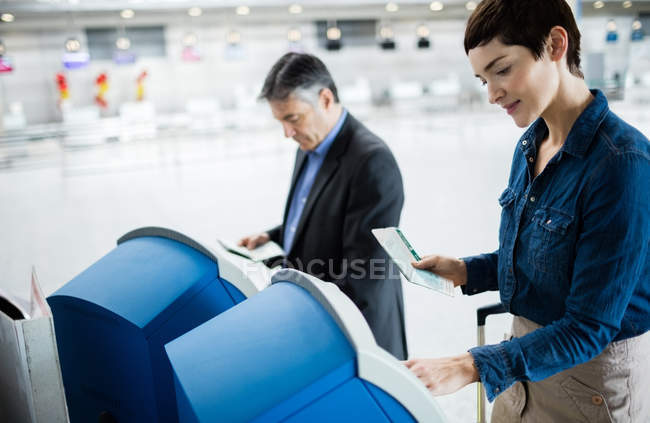 Business people using self service check-in machines at airport — Stock Photo