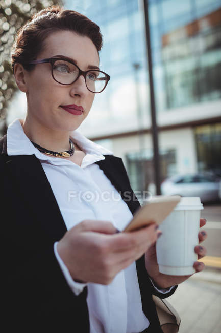 Pretty businesswoman holding cellphone and disposable coffee cup on sidewalk — Stock Photo