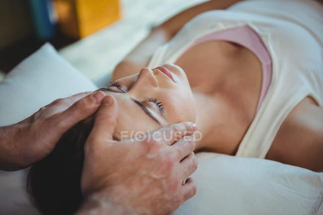 Physiotherapeut gibt Patientin in Klinik Kopfmassage — Stockfoto