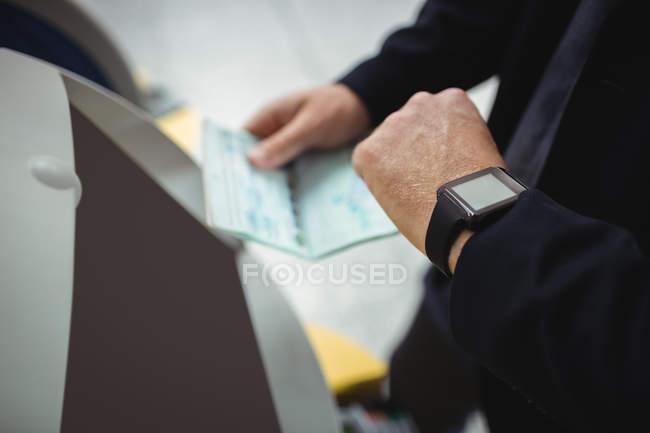 Mains d'homme d'affaires à l'aide de self-service machine d'enregistrement automatique à l'aéroport — Photo de stock