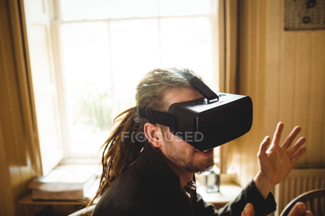 Close-up of young hipster gesturing while using virtual reality simulator at home — Stock Photo