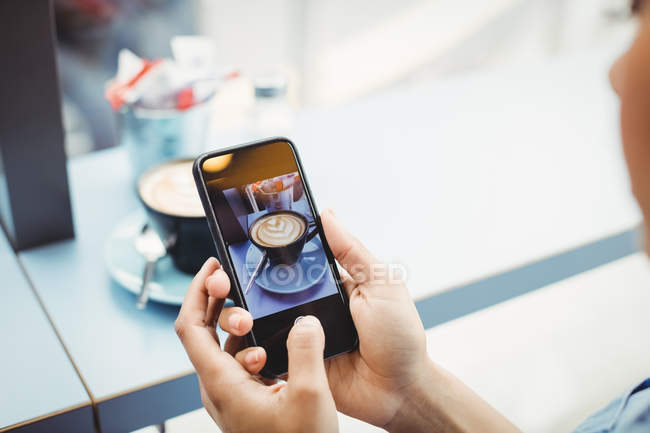 Woman holding mobile phone with photograph of coffee at restaurant — Stock Photo